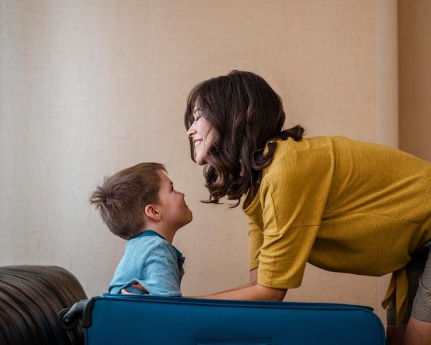 Mulher de tiro médio e criança com bagagem