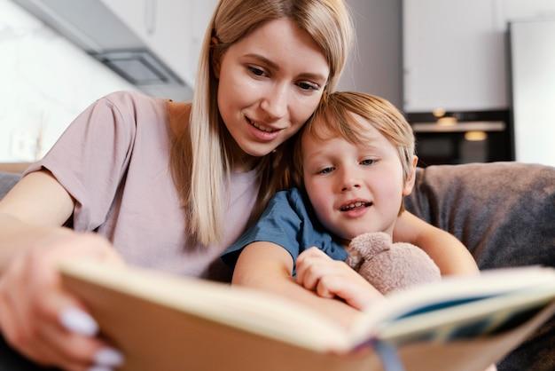 Mulher de tiro médio e criança lendo