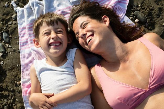 Mulher de tiro médio e criança na toalha