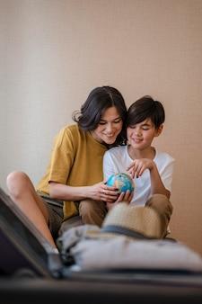 Mulher de tiro médio e criança segurando um globo