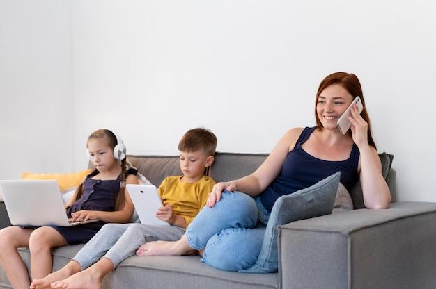 Mulher de tiro médio e crianças com dispositivos