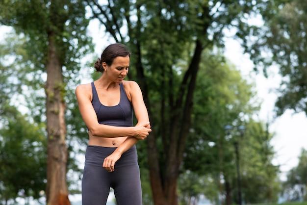 Mulher de tiro médio experimentando dor no cotovelo