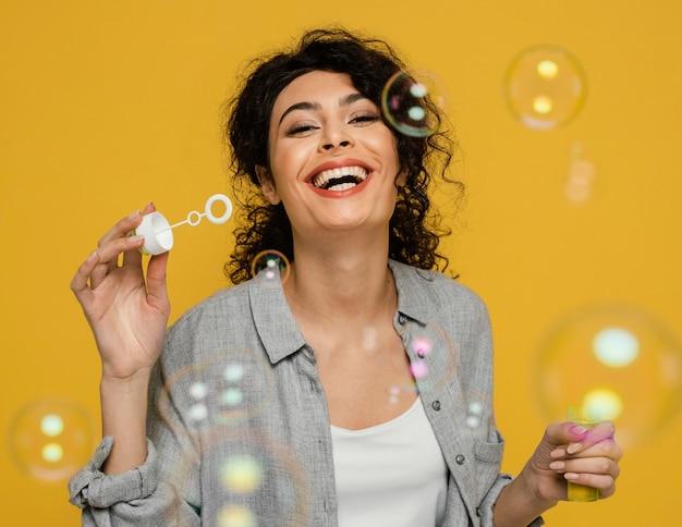 Mulher de tiro médio fazendo bolhas de sabão