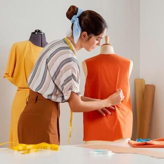 Mulher de tiro médio fazendo roupas