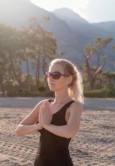 Mulher de tiro médio meditando ao ar livre