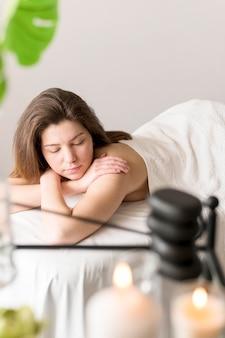 Mulher de tiro médio na mesa de massagem