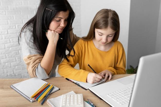 Mulher de tiro médio olhando para a garota escrevendo