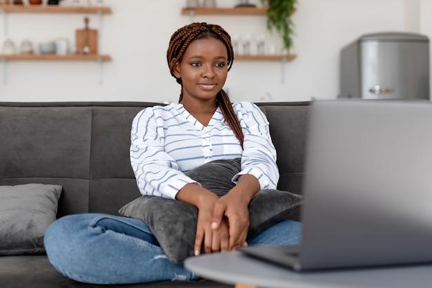 Mulher de tiro médio olhando para um laptop