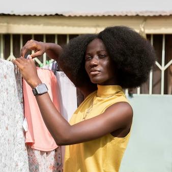 Mulher de tiro médio pendurando roupas para secar