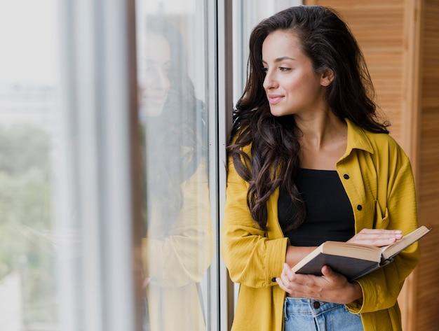 Mulher de tiro médio perto da janela com livro