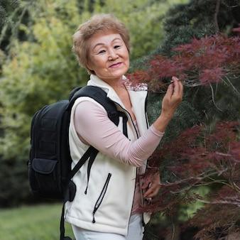 Mulher de tiro médio posando com árvore