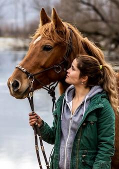 Mulher de tiro médio posando com cavalo