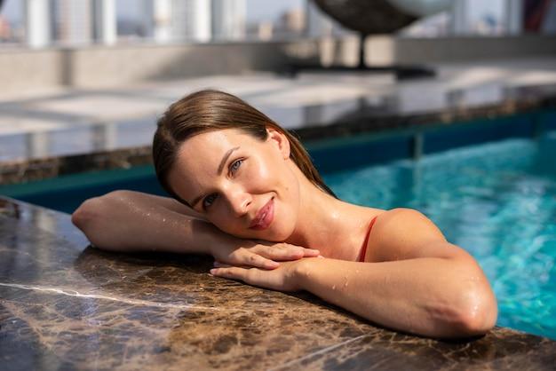 Mulher de tiro médio posando na piscina