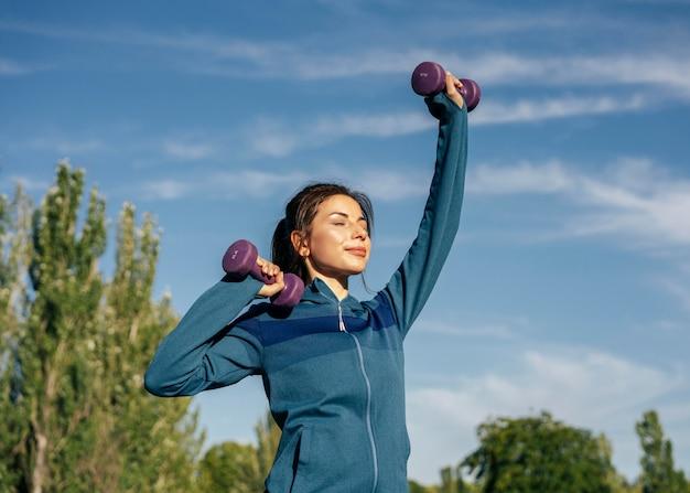 Mulher de tiro médio praticando com halteres