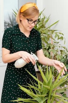 Mulher de tiro médio regando planta de casa