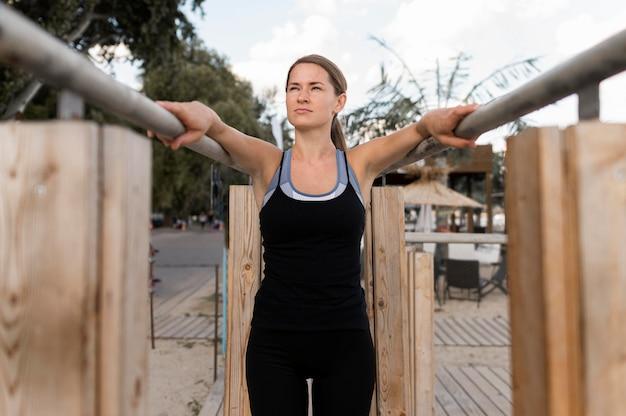 Mulher de tiro médio se exercitando em roupas esportivas