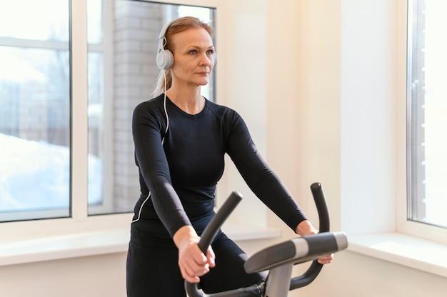 Mulher de tiro médio se exercitando em uma bicicleta de spinning