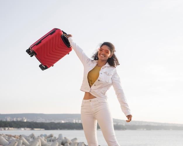 Mulher de tiro médio segurando bagagem