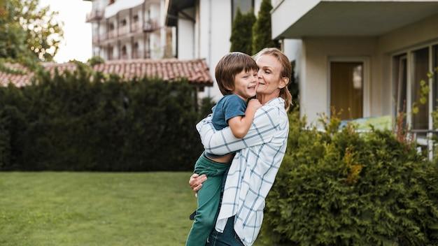 Mulher de tiro médio segurando criança feliz