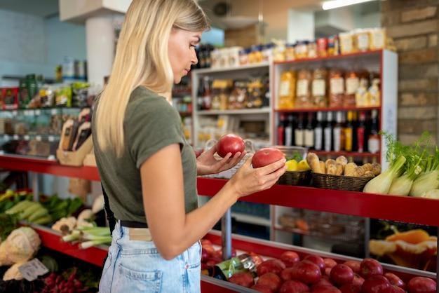 Mulher de tiro médio segurando frutas