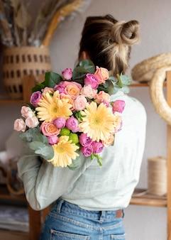 Mulher de tiro médio segurando um buquê de flores