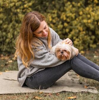 Mulher de tiro médio segurando um cachorro fofo