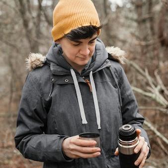 Mulher de tiro médio segurando um frasco