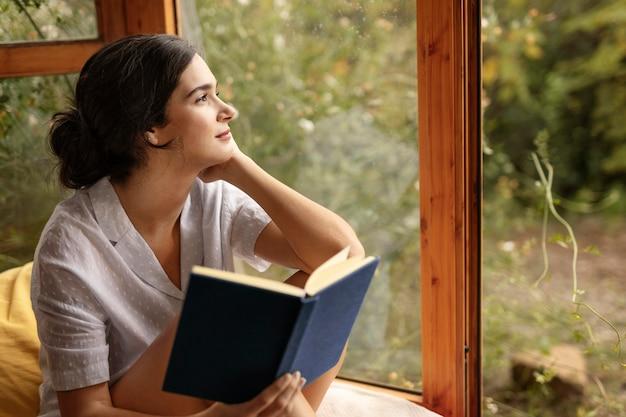 Mulher de tiro médio segurando um livro