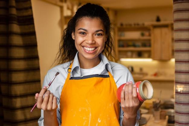 Mulher de tiro médio segurando um pote de barro