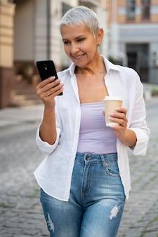 Mulher de tiro médio segurando um smartphone