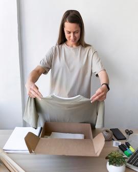Mulher de tiro médio segurando uma camisa