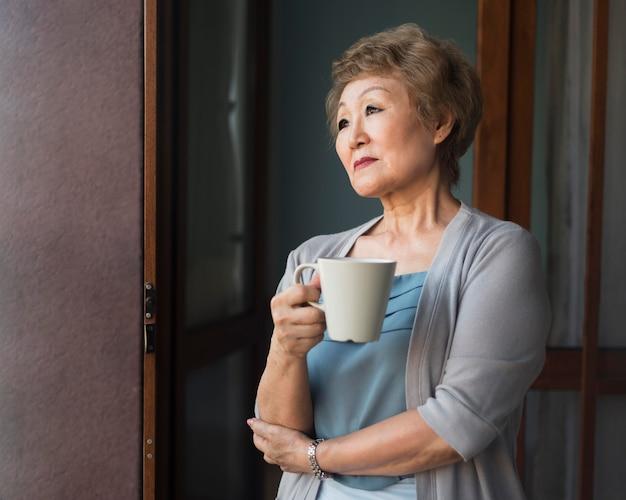 Mulher de tiro médio segurando uma caneca de café
