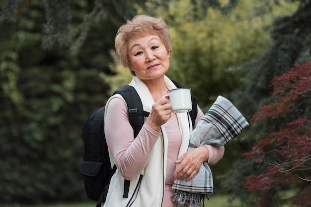 Mulher de tiro médio segurando uma caneca