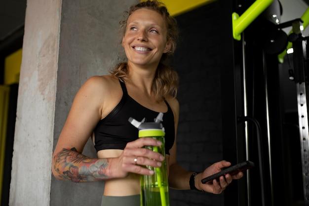 Mulher de tiro médio segurando uma garrafa de água