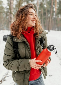 Mulher de tiro médio segurando uma garrafa