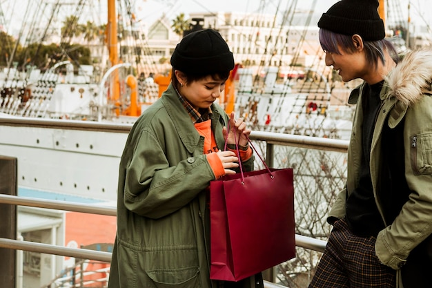 Mulher de tiro médio segurando uma sacola de compras