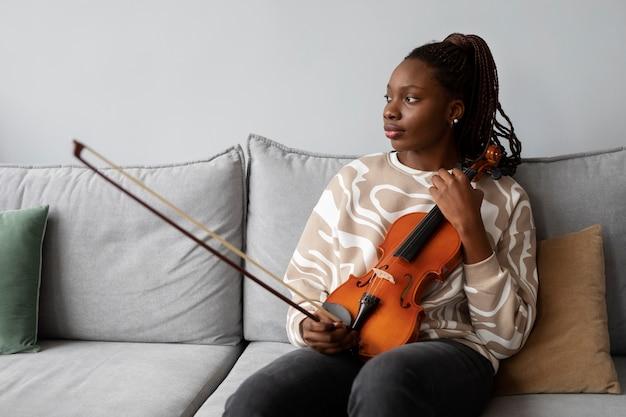 Mulher de tiro médio segurando violino