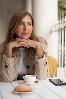 Mulher de tiro médio sentada à mesa