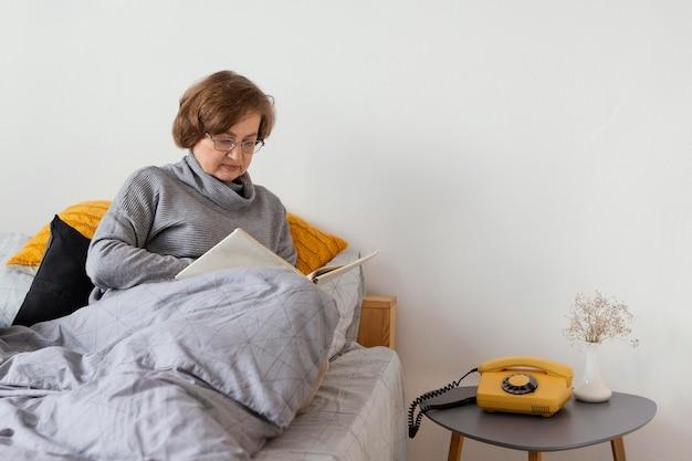 Mulher de tiro médio sentada na cama