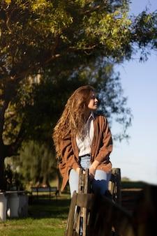 Mulher de tiro médio sentada na cerca