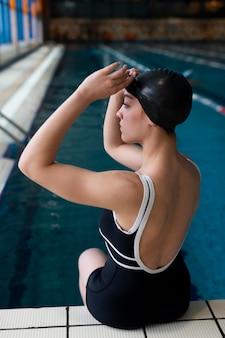 Mulher de tiro médio sentada perto da piscina