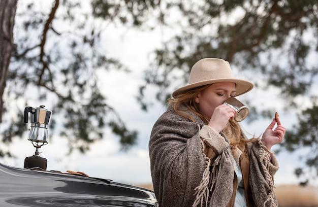 Mulher de tiro médio tomando café