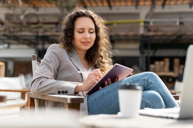 Mulher de tiro médio trabalhando com tablet