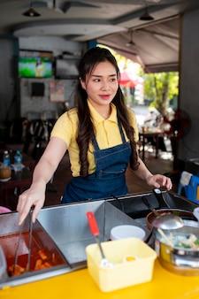 Mulher de tiro médio trabalhando em um food truck