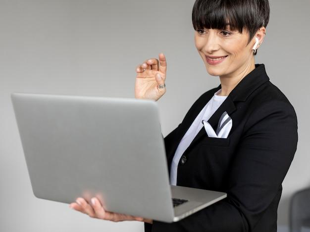 Mulher de tiro médio trabalhando em um laptop