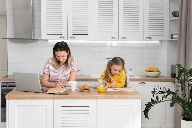 Mulher de tiro médio trabalhando em uma mesa com uma garota