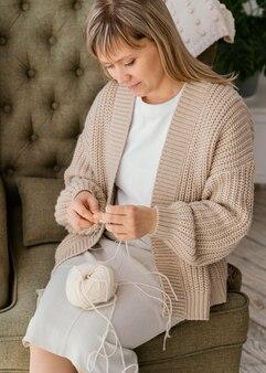 Mulher de tiro médio tricotando ângulo alto