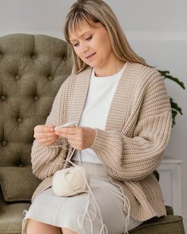 Mulher de tiro médio tricotando por dentro