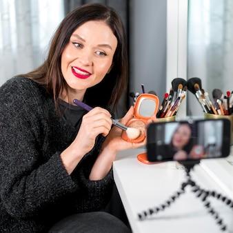 Mulher de tiro médio usando maquiagem