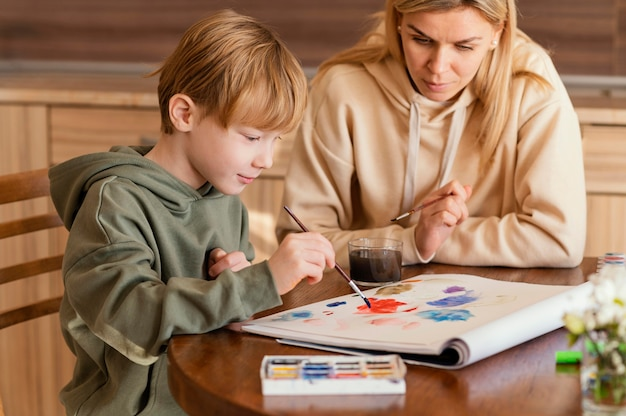 Mulher de tiro médio vendo criança pintar